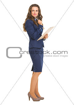 Full length portrait of thoughtful business woman with clipboard
