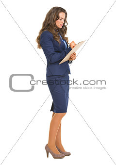 Full length portrait of business woman writing something in clip