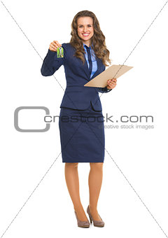 Smiling realtor woman with clipboard giving keys