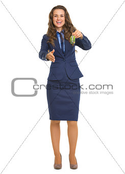 Smiling realtor woman giving keys and stretching hand for handsh