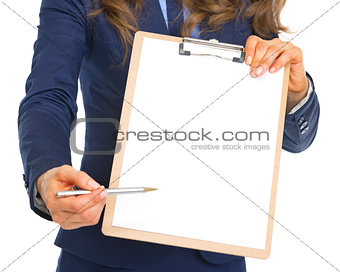 Closeup on business woman giving clipboard for sign