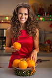 Happy young housewife decorating christmas plate with oranges