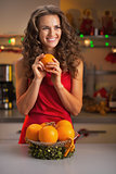 Happy young housewife with oranges in christmas decorated kitche