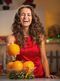 Happy young woman showing orange in christmas decorated kitchen