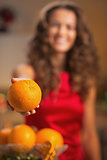 Closeup on orange in hand of young housewife in kitchen