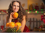 Thoughtful young housewife with orange in christmas decorated ki