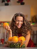 Happy young housewife with orange in christmas decorated kitchen