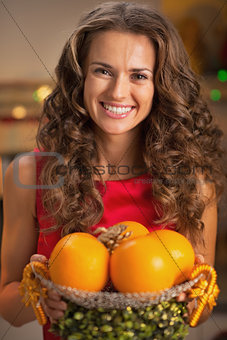 Portrait of smiling young housewife holding christmas decorated
