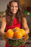 Closeup on christmas decorated plate with oranges in hand of you