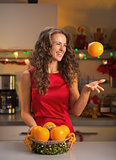 Happy young woman throwing up orange in christmas decorated kitc