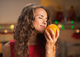 Happy woman enjoying orange in christmas decorated kitchen
