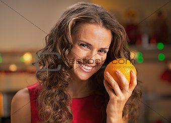 Portrait of smiling young housewife with orange in christmas dec