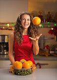 Smiling young woman throwing up orange in christmas decorated ki