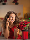 Smiling young housewife talking phone and playing with christmas