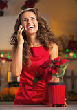 Happy young housewife talking phone in christmas decorated kitch