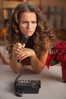 Serious young housewife holding phone set