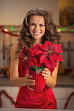 Happy young woman in red dress holding christmas rose in christm