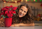 Smiling young woman looking out from christmas rose in christmas