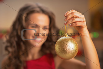 Closeup on christmas ball in hand of woman in red dress