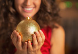 Closeup on christmas ball in hand of smiling woman in red dress