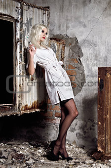 Beautiful young girl in the image of nurse standing among ruins