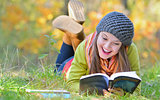 beautiful girl with book in autumn park