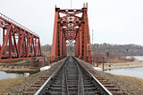 Red metal railway bridge across the river.