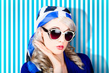 Beautiful retro pinup girl in scarf and sunglasses