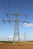 Electricity pylons and lines on a field