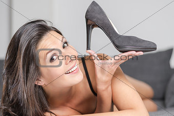 Attractive woman holding up an elegant shoe, beauty and fashion