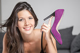 Attractive woman holding up an elegant shoe