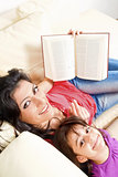 Mother and daughter smile while reading a book