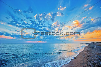Sunset sky over the sea, sandy beach.