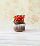 Chocolate cupcake with red currant in the romantic scenery