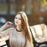 beautiful red hair young woman sitting on bench