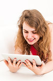 young woman on the couch with her tablet