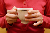 Woman holding a teacup in two hands