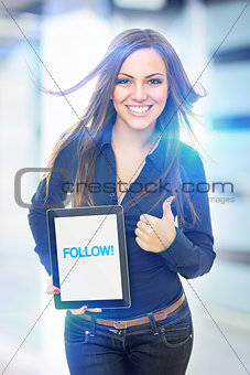 Cute young woman holding tablet that states follow