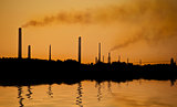 Industrial chimney stacks in natural landscape polluting the air