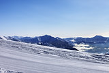 Ski slope and snowy mountain in haze