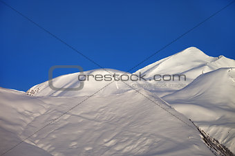 Off-piste slope and blue clear sky in nice winter morning
