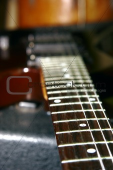 close up of guitar neck on blurred background