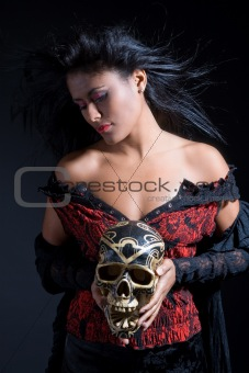 Beautiful brazilian woman holding a skull