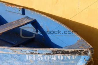 old blue boat and yellow wall