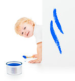 Baby boy with paint brush on all fours behind painted white wall