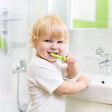 Kid boy brushing teeth in bathroom