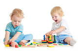 Two kids playing wooden toys together sitting