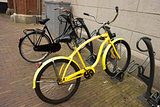 yellow bike with flat tyre parked in a bicycle parking