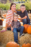 Portrait of Attractive Mother and Her Sons at Pumpkin Patch