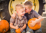 Two Boys Sitting Against Tractor Tire Holding Pumpkins Whisperin